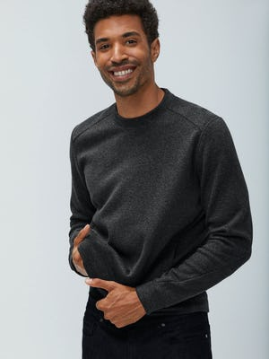 Men's Charcoal Heather Hybrid Fleece Crewneck Sweatshirt on model adjusting bottom of sweater