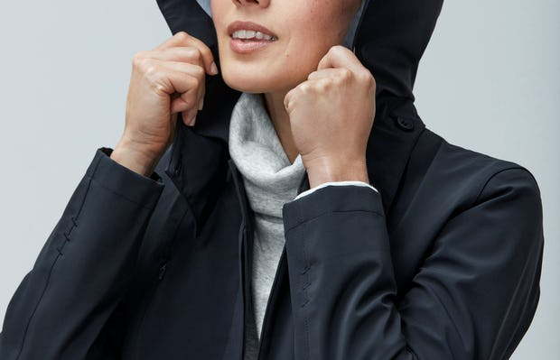 Close up of Women's Marble Hybrid Funnel Neck and Women's Black Doppler Mac on model with hood up
