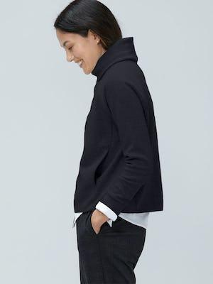 model wearing black hybrid funnel neck facing left with hands in pockets