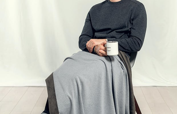 Man sitting in chair holding cup of coffee with Granite Hybrid Everywhere Blanket laying a