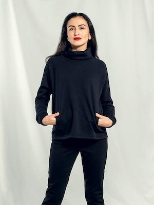 Woman wearing Women's Black Hybrid Fleece Funnel Neck with hands in pockets