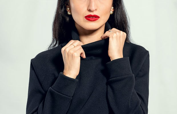 Woman wearing Women's Black Hybrid Fleece Funnel Neck adjusting collar