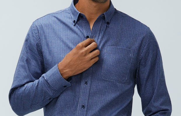 Men's indigo heather gingham aero button down model facing forward with hand in pocket buttoning shirt