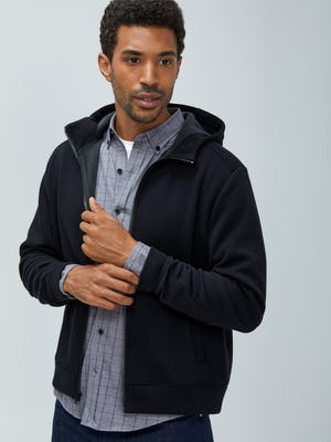 Men's Black Hybrid Fleece Full Zip Hoodie layered over Men's Aero Button Down Grey Heather Merlot on model adjusting sleeves