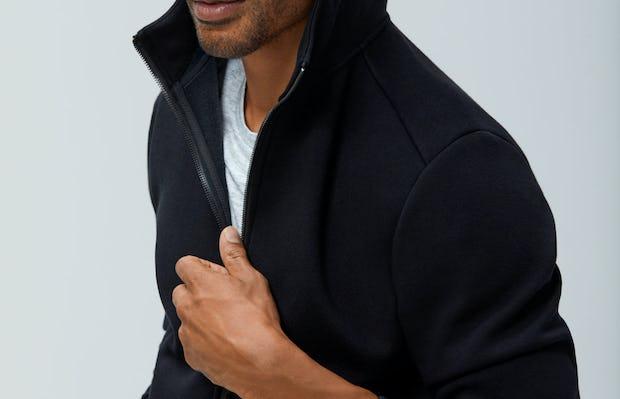 Men's Black Hybrid Fleece Full Zip Hoodie on model with hood up adjusting zipper