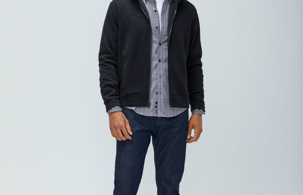 Men's Black Hybrid Fleece Full Zip Hoodie layered over Men's Aero Button Down Grey Heather Merlot and Men's Indigo Chroma Denim on Model facing forward