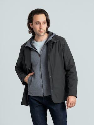 model wearing charcoal kinetic light layer and granite heather hybrid full zip hoodie facing forward hand in hoodie pocket