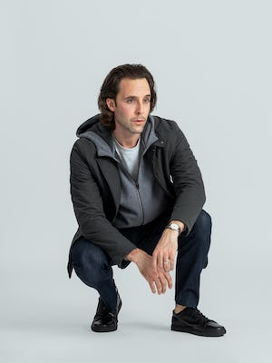 model wearing charcoal kinetic light layer and granite heather hybrid full zip hoodie and indigo chroma denim pant crouched down