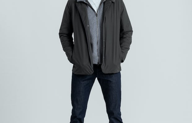 model wearing charcoal kinetic light layer and granite heather hybrid full zip hoodie and indigo chroma denim pant facing forward hands in pockets