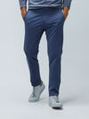 Men's Indigo Heather Kinetic Pants on Model walking forward with hands in pockets