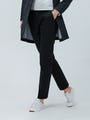 Women's Black Kinetic Slim Pant on Model walking forward with hand in pocket