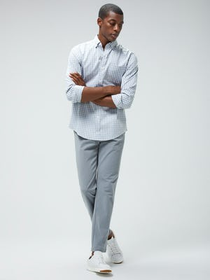 Men's Blue Grey Tattersall Aero Button Down and Men's Light Grey Momentum Chino on model walking forward with arms crossed