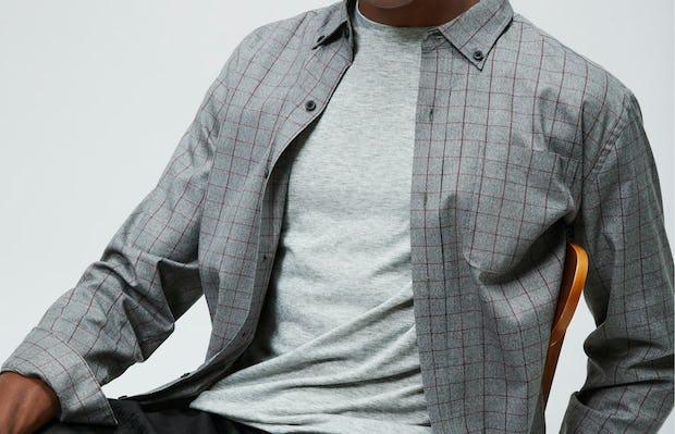 Men's Pale Grey Heather Composite Merino Tee under Men's Stone Grey Fusion Chore Coat on model sitting in chair