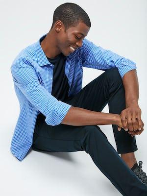 Men's Blue Grid Aero Zero Carbon Neutral Shirt and Men's Navy Kinetic Slim Pant on Model sitting