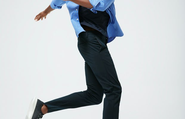 Men's Blue Grid Aero Zero Carbon Neutral Shirt and Men's Navy Kinetic Slim Pant on Model jumping