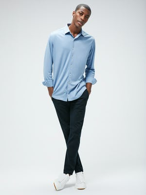 Men's Deep Sky Blue Oxford Apollo Brushed Shirt and Men's Navy Kinetic Pant on model with legs crossed