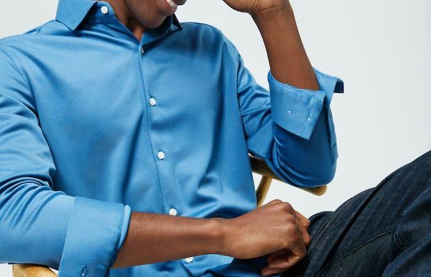 Men's Storm Blue Apollo Brushed Shirt and Men's Indigo Chroma Denim on model sitting in chair