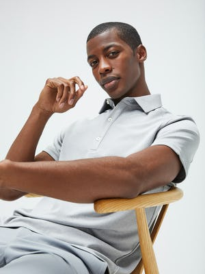 Men's Grey White Heather Apollo Polo and Men's Light Grey Momentum Chino on model sitting in chair
