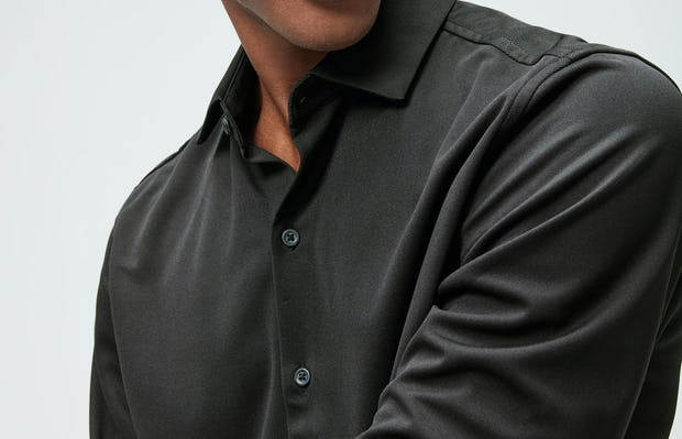 Close up of Men's Black Recycled Apollo Shirt on model adjusting sleeve