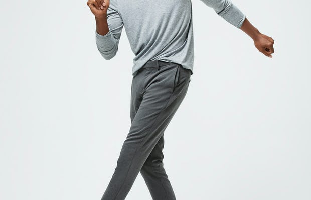 Men's Charcoal Grey Heather Composite Merino Long Sleeve Tee and Men's Graphite Velocity Tapered Pant on model kicking leg up