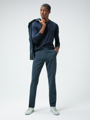 Men's Navy Composite Merino Long Sleeve tee and Men's Blue Houndstooth Velocity Houndstooth Pant on model with blazer slung over shoulder