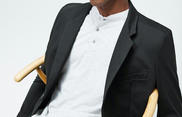 Men's Grey Heather Composite Merino Short Sleeve Henley under Men's Black Kinetic Blazer on model sitting in chair