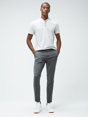 Men's Grey Heather Composite Merino Short Sleeve Henley and Men's Graphite Velocity Tapered Pant on model with hands in pockets