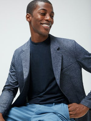 Men's Navy Composite Merino Tee under Men's Navy Heather Kinetic Dot Air Blazer on model sitting in chair