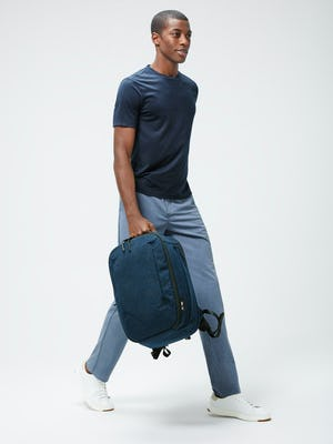 Men's Navy Composite Merino Tee and Men's Calcite Heather Velocity Pant on model walking right carrying AER x MoS Lunar Pack