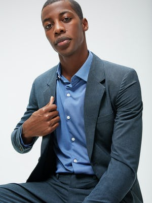 Men's Ocean Oxford Recycled Apollo Brushed Shirt and Men's Blue Houndstooth Velocity Houndstooth Blazer on model sitting in chair adjusting blazer