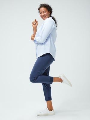 Women's Chambray Blue Aero Zero Boyfriend Shirt and Women's Slate Blue Kinetic Pull-On Pant on model facing left kicking up leg
