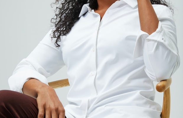 Women's White Aero Zero Carbon Neutral Shirt and Women's Ruby Swift Drape Pant on model sitting in chair