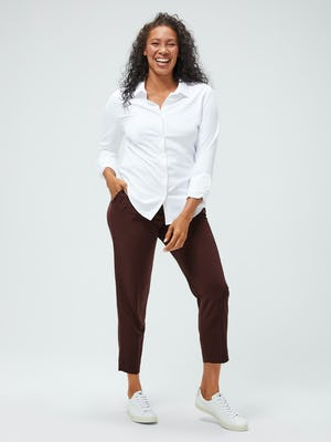 Women's White Aero Zero Carbon Neutral Shirt and Women's Ruby Swift Drape Pant on model facing forward with hand in pocket