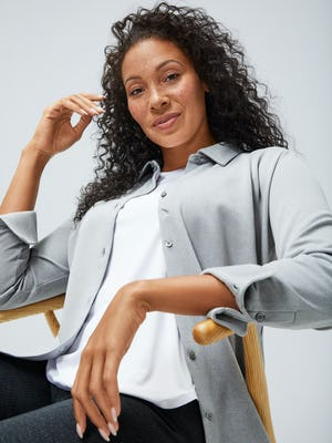 Women's White Luxe Touch Tank under Women's Grey Heather Brushed Apollo Shirt on model sitting in chair