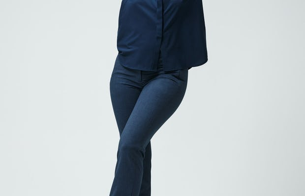 women's navy juno blouse and azurite heather velocity pant model stepping forward sleeves cuffed hands on head