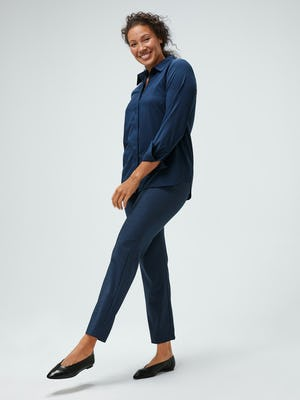 women's navy juno blouse and azurite heather velocity pant model facing forward extending leg sleeve cuffed