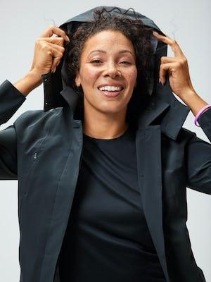 women's black luxe touch tank and black doppler mac raincoat model putting hood on