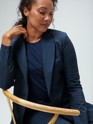 women's azurite heather velocity blazer and navy composite merino tank on model sitting in chair