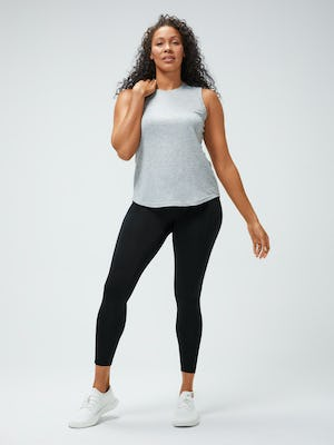 women's pale grey heather composite merino active tank and black joule active legging model facing forward hand on shoulder