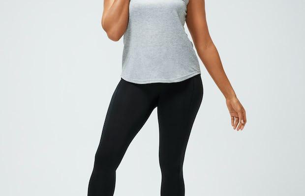 women's pale grey heather composite merino active tank and black joule active legging model facing forward hand on shoulder