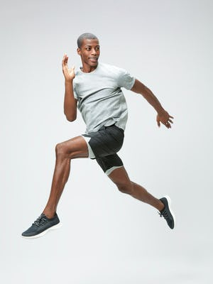 Men's Charcoal Grey Heather Composite Merino Active Tee and Men's Black Newton Active Shorts on model jumping in air