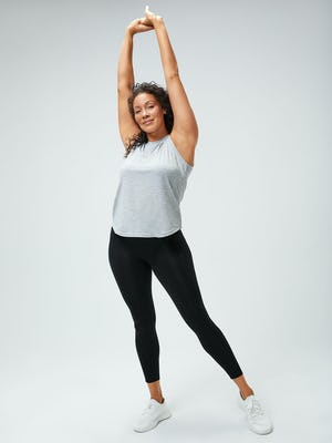 women's pale grey heather composite merino active tank and black joule active legging model facing forward stretching hands over her head