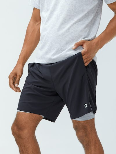 close up of men's black newton active short on model hand in pocket