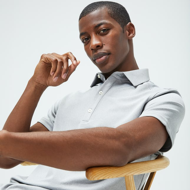 Man wearing grey Apollo polo sitting in a chair