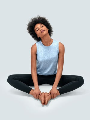women's chambray blue composite merino active tank and joule active legging model doing a sitting stretch