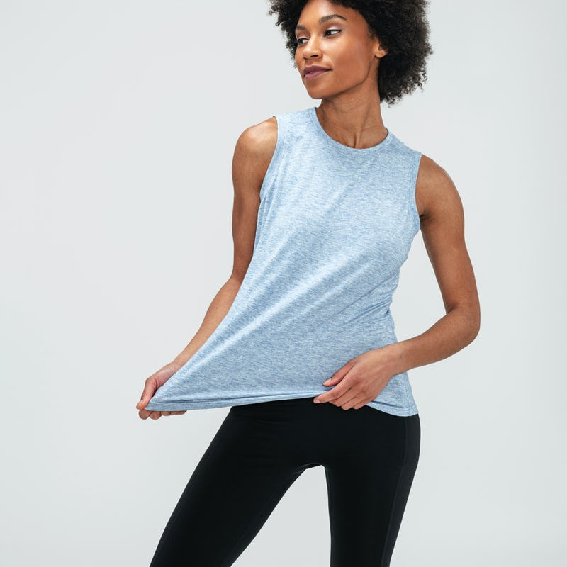 woman wearing blue tank and stretching it at the hem