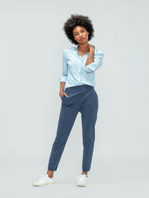 Women's Light Blue Juno Recycled Tailored Shirt and Women's Slate Blue Kinetic Pull-On Pant on model facing forward hand on neck