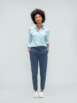 Women's Light Blue Juno Recycled Tailored Shirt and Women's Slate Blue Kinetic Pull-On Pant on model facing forward hands in pockets