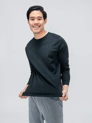 Men's Charcoal Static Atlas Crew Neck Sweater and Men's Light Grey Momentum Chino on model stretching sweater