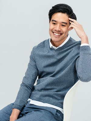Men's Indigo Static Atlas V-Neck Sweater and Men's Calcite Heather Velocity Pants on model sitting in chair